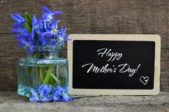 Happy Mother`s Day greeting card with Scilla siberica blue spring flowers in a glass vase and chalkboard with text on old wooden b. Ackground.Snowdrops bouquet royalty free stock photography