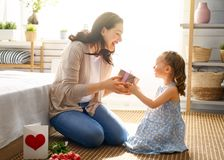 Happy mother`s day. ! Child daughter is congratulating mom and giving her flowers tulips. Mum and girl smiling. Family holiday and togetherness royalty free stock photo