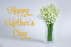 Happy Mother`s Day and a lilies of the valley in a glass cup on a simple background royalty free stock image