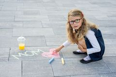 Happy Mother`s Day. A little girl draws for her mother a picture surprise of crayons on the asphalt. Royalty Free Stock Image