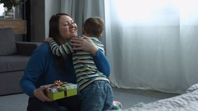 Cute son giving gift box to mom on Mother`s Day. Happy mother`s day! Loving little son congratulating his charming mother and giving her gift box in domestic