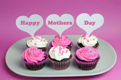 Happy Mother's Day message across white heart toppers on pink and white decorated red velvet cupcakes Royalty Free Stock Images