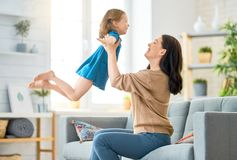Mother and daughter playing. Happy mother`s day! Mom and her daughter child girl are playing, smiling and hugging. Family holiday and togetherness stock photos