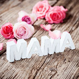 Happy Mother's Day!. Paper letters saying the word Mama on rustic wooden background and roses Stock Photo