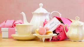 Mother`s Day tea setting with teapot, macaron cookies, pink roses and gift. Royalty Free Stock Images