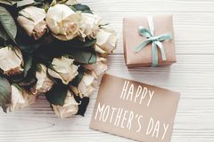 Happy Mother`s Day text sign on craft greeting card and white roses bouquet, gift box on wooden background, flat lay. Mothers day stock photo