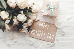 Happy Mother`s Day text sign on craft greeting card and white roses bouquet, gift box on wooden background, flat lay. Mothers day royalty free stock image