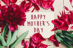 Happy mother`s day text sign on craft paper card beautiful red p. Eonies on wooden rustic background, flat lay. modern greeting card. mothers day. stylish royalty free stock photos