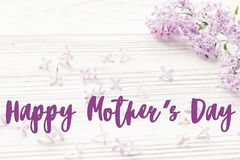 Happy mother`s day text sign. greeting card. gentle pink lilac f. Lowers on white rustic wooden background. tender soft image. mothers day concept stock photo