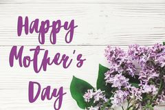 Happy mother`s day text sign. greeting card. gentle purple lilac. Flowers on white rustic wooden background. tender soft image. mothers day concept. flat lay royalty free stock image