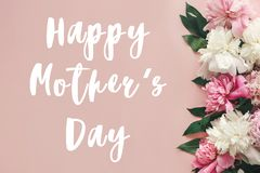 Happy Mother`s Day text sign on peonies flat lay. Pink and white peonies border on pastel pink paper with space for text. Stylis. H floral greeting card stock images