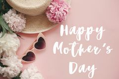 Happy Mother`s Day text sign at stylish girly pink retro sunglasses, white and pink peonies, straw hat on pastel pink paper. Stylish floral greeting card royalty free stock image
