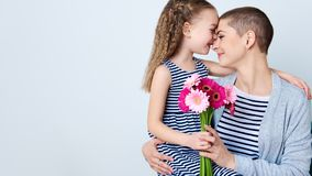 Happy Mother`s Day, Women`s day or Birthday background. Cute little girl giving mom bouquet of pink gerbera daisies. Loving mother. And daughter smiling and Royalty Free Stock Photography