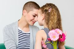 Happy Mother`s Day, Women`s day or Birthday background. Cute little girl giving mom, cancer survivor, bouquet of flowers. Happy Mother`s Day, Women`s day or stock photos