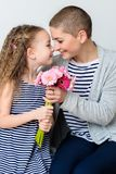 Happy Mother`s Day, Women`s day or Birthday background. Cute little girl giving mom, cancer survivor, bouquet of flowers. Happy Mother`s Day, Women`s day or stock image