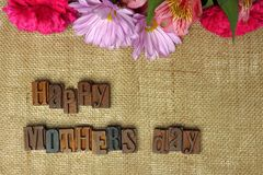 Happy Mother's Day wooden letters on burlap with flowers Royalty Free Stock Image