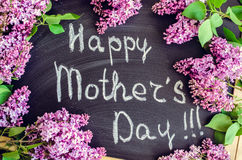 Happy Mother`s Day. Wording Happy Mother`s Day on chalkboard background with lilac flowers Royalty Free Stock Image