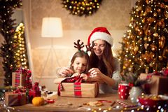 A happy family mother and child pack Christmas gifts. Happy mother in santa helper hat and little girl in Christmas deer antlers pack Christmas gifts and have royalty free stock images