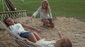 Happy mother shakes her daughters in hammock slow motion stock footage video stock video footage