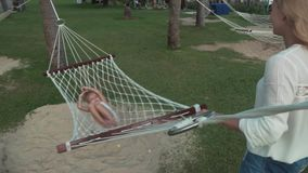 Happy mother shakes her daughters in hammock slow motion stock footage video stock footage