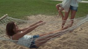 Happy mother shakes her daughters in hammock stock footage video stock video