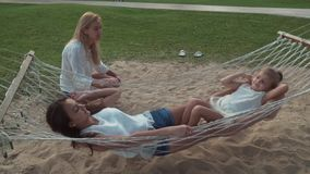 Happy mother shakes her daughters in hammock stock footage video stock footage