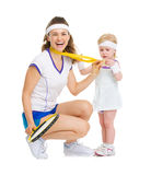 Happy mother showing baby medal for achievements in tennis. Isolated on white Royalty Free Stock Photos
