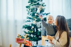 Happy mother showing Christmas ball to baby near Christmas tree Royalty Free Stock Images