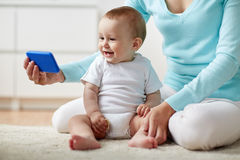 Happy mother showing smartphone to baby at home Stock Images