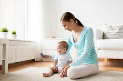 Happy mother showing smartphone to baby at home Royalty Free Stock Photo
