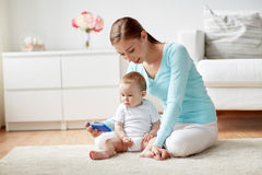Happy mother showing smartphone to baby at home Royalty Free Stock Photos
