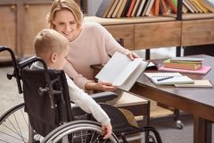 Happy mother showing something in book to son. On wheelchair Stock Photo