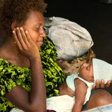 Happy mother with newborn baby. Mum looking gladly to newborn child, Rabaul, Papua New Guinea