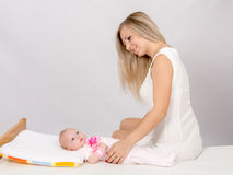 Happy mother sitting on a bed and looking at a two-month daughter Stock Photos
