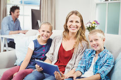 Happy mother sitting with children on sofa Royalty Free Stock Photos