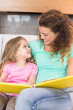 Happy mother sitting with her little daughter reading a storybook Stock Photos