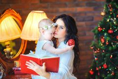 Mother sitting near the mirror holding a small daughter, on the background of a festive Christmas tree stock photo