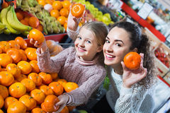Happy mother and small daughter buying citrus Stock Photos