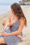 Happy Mother and small daughter go along the seashore Stock Photos