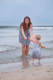 Happy Mother and small daughter go along the seashore Stock Photo
