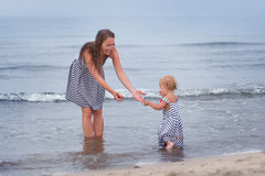 Happy Mother and small daughter go along the seashore Royalty Free Stock Photos