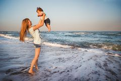 Happy mother and small daughter playing together at beach. Mom i. S throwing her kid in the air stock photos