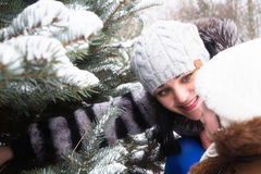 Happy mother with small daughter in winter park near fir-tree Royalty Free Stock Photos