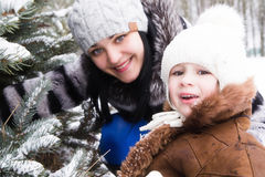 Happy mother with small daughter in winter park near fir-tree Royalty Free Stock Photo