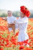 A happy mother with a small son in her arms on the endless field of red poppies on a sunny summer day Royalty Free Stock Photos