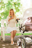 Happy mother with smartphone and stroller in park Stock Image