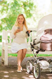 Happy mother with smartphone and stroller in park Royalty Free Stock Images