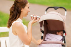 Happy mother with smartphone and stroller at park Stock Photography