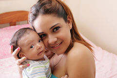 Happy mother with smiling baby. Portrait of a beautiful hispanic happy mother with smiling baby Stock Photography