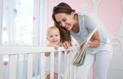 Happy mother with smiling baby together in bedroom Stock Photos